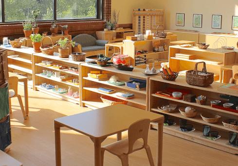 Une classe aménagée avec le matériel Montessori et les tables individuelles