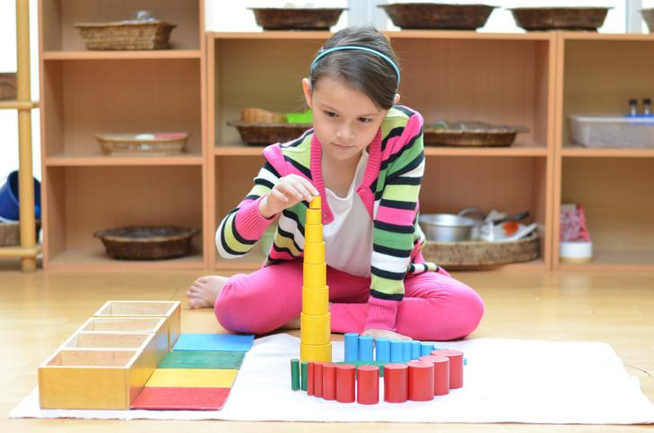 """Elève travaillant l'affinement de ses sens avec le matériel Montessori """"Les cylindres de couleur"""""""