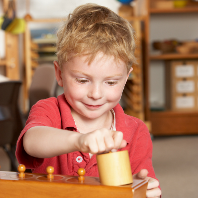 Enfant s'exerçant au bloc des cylindres, matériel Montessori très apprécié des enfants