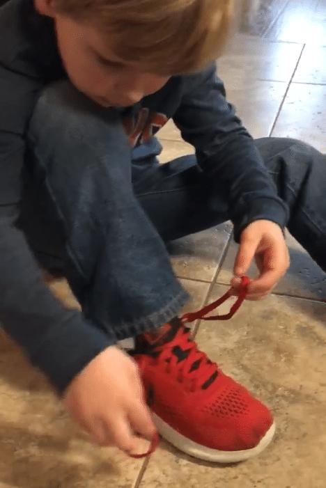 Enfant faisant lui-même ses lacets